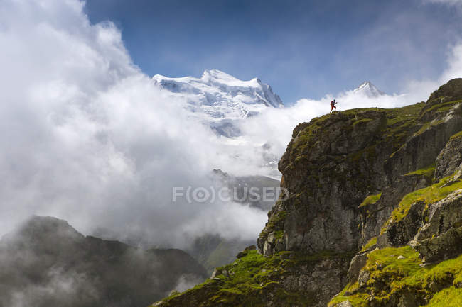 Hiker walking up steep ridge with mountain range in background — Stock Photo