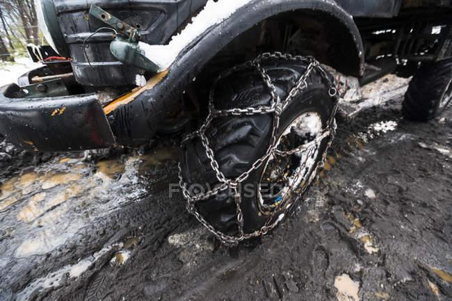 Тяжелых грузовиков с цепочкой шины, проезжая через грязь и снег — стоковое фото