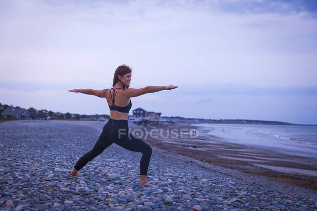 Woman In Warrior 2 Pose Doing Yoga At Sunset In The Summer — Stock Photo
