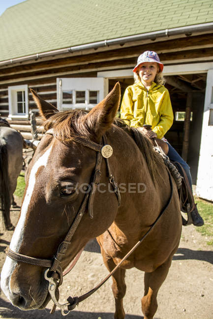 Young girl sitting on horse for horseback riding — Photo de stock