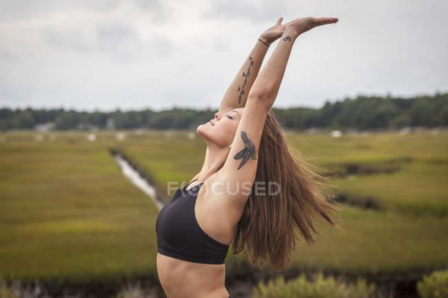 Donna che fa Yoga che si appoggia indietro In un Backbend fuori su una stuoia di Yoga — Foto stock