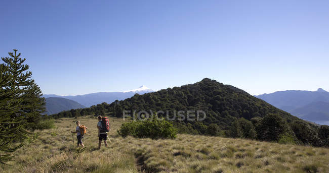 Couple of hikers on alpine ridge with volcano behind — Stock Photo