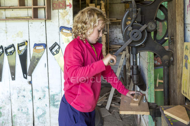 Young Girl Working With Drill In Workshop — стокове фото
