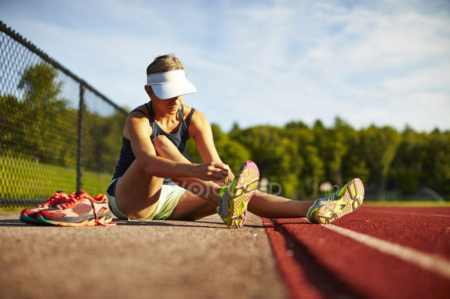 A Woman Changes Shoes Before Her Track Workout — Stock Photo