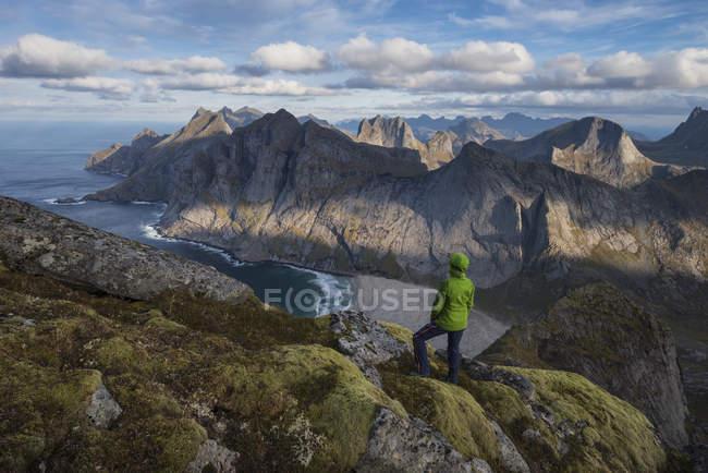 Female hiker taking in view over Bunes beach while hiking to Storskiva mountain peak, Moskenesy, Lofoten Islands, Norway — Stock Photo