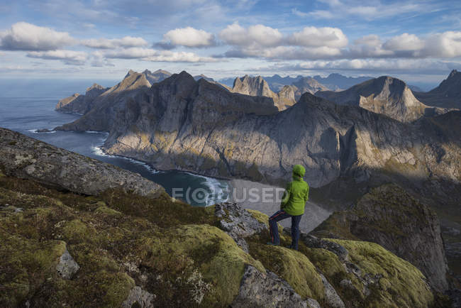 Female hiker taking in view over Bunes beach while hiking to Storskiva mountain peak, Moskenesy, Lofoten Islands, Norway — Stock Photo