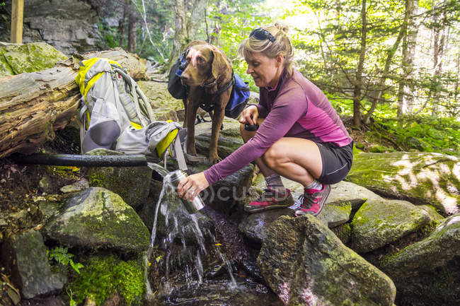 A Woman With Her Dog Filling Her Water Bottle In Shanty Spring — Stock Photo