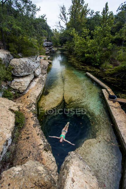 Woman lying in swimming hole between rocks — стоковое фото