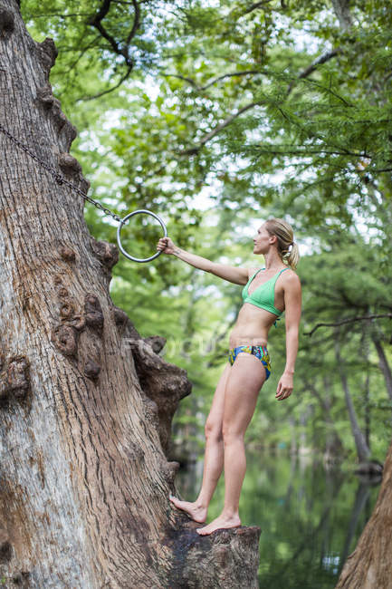 Young woman holding rope swing by lake — Foto stock