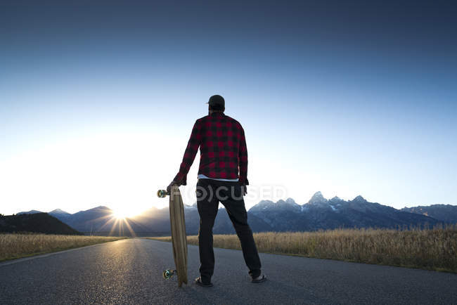 A skateboarder pauses to watch the sun set over the Grand Teton Mountains in Jackson Hole, Wyoming. — Stock Photo