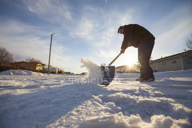 Senior schaufelt Schnee von Einfahrt — Stockfoto