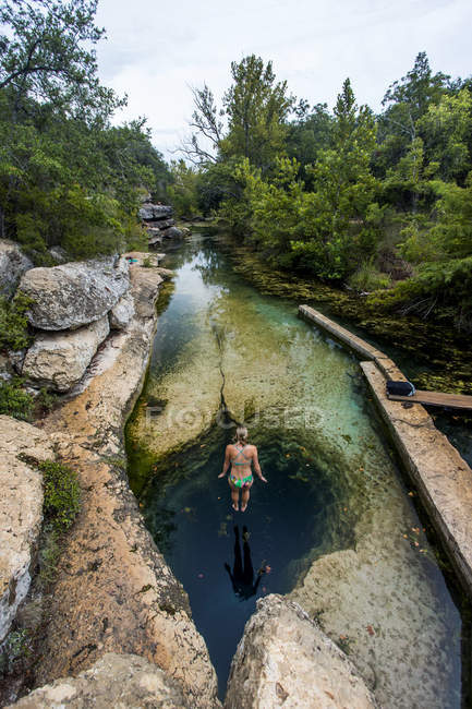 Woman jumping in swimming hole between rocks — стоковое фото