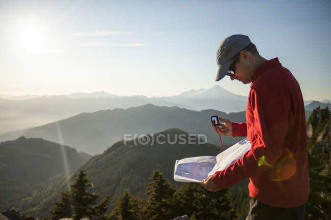 Un uomo utilizza una mappa di carta e bussola per navigare durante le escursioni nella catena montuosa Nord Cascade — Foto stock