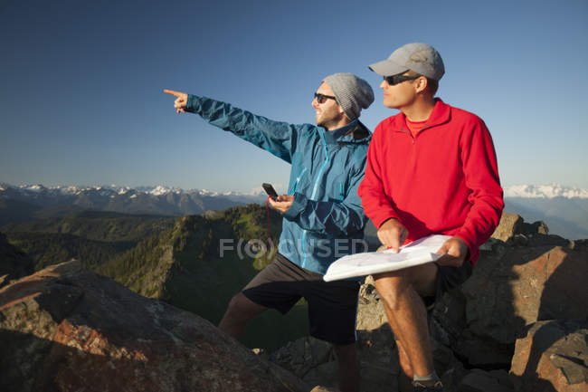 Two men use a paper map and a compass to identify nearby peaks while hiking in the North Cascade Mountain Range. — Stock Photo