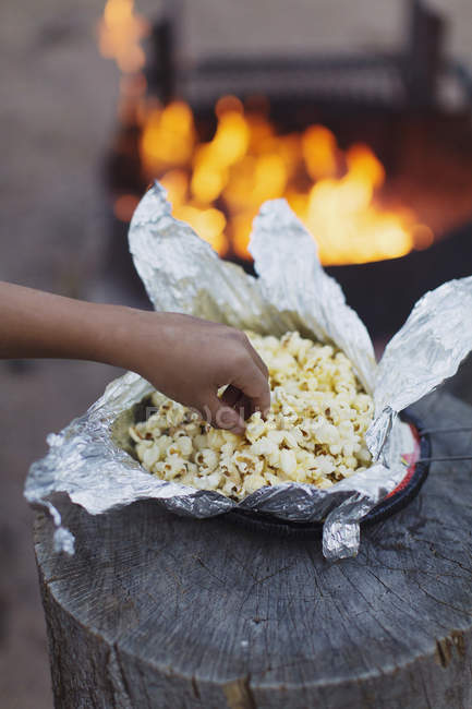 Main de garçon prenant pop-corn du papier d'aluminium avec flamme à fond — Photo de stock
