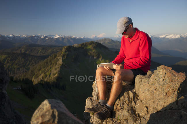 A man works on his tablet while sitting on a rocky bluff near the summit of Sauk Mountain, Washington. — Stock Photo