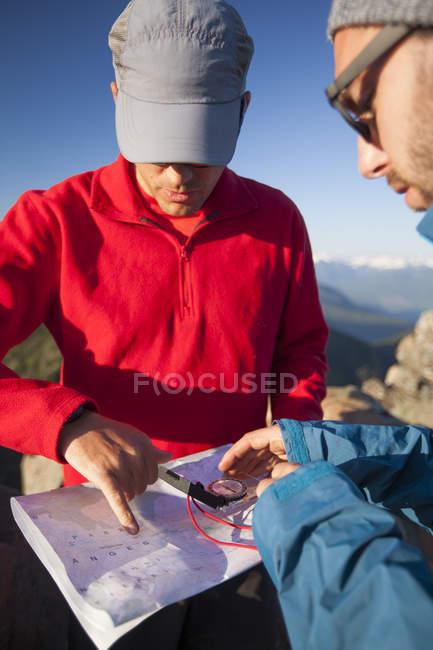 Due uomini utilizzano una mappa cartacea e una bussola per navigare durante le escursioni nella catena montuosa Nord Cascade — Foto stock