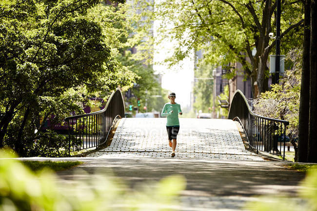 A Woman Running On Bridge Along The Charles River In Boston — Stock Photo
