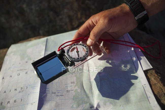 Человек использует компас и бумажные карты для навигации. — стоковое фото