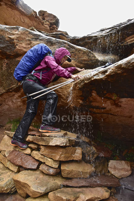 Woman Climbing Rock Navigating Waterfall In Canyonlands National Park — Stock Photo