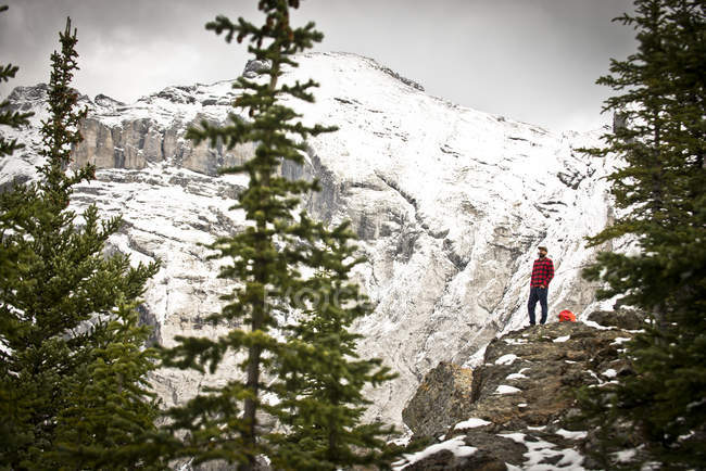 A guy in a red and black flannel stands on a mountain cliff in Banff national Park, Canada. — Stockfoto