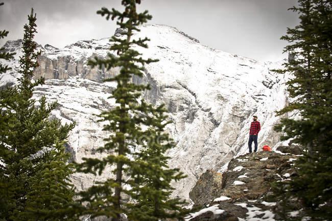 Ein kerl in einem rot-schwarzen flanell steht auf einer bergklippe im banff nationalpark, kanada. — Stockfoto