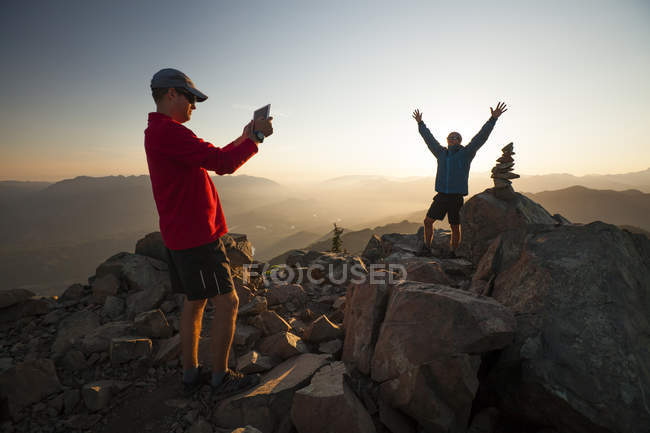 A hiker uses a tablet to take a picture of his friend standing next to the summit cairn of Sauk Mountain, Washington. — Stock Photo