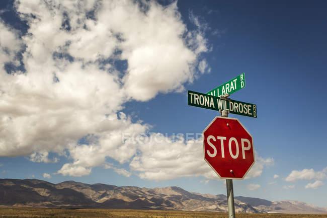 Stop-Schild und zwei Straßenschilder mit Wüste Berge am Horizont und ein großer, blauer Himmel mit geschwollenen Wolken — Stockfoto