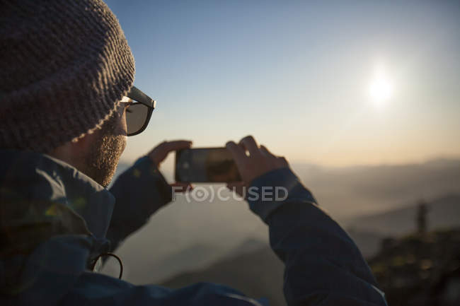A man uses his phone to snap a photo of the view from the summit of Sauk Mountain in the North Cascades, Washington. — Stock Photo