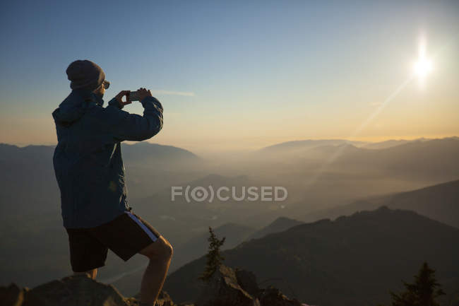 A hiker uses his smartphone to take a photo of the view from the summit of Sauk Mountain in the North Cascades, Washington. — Stock Photo