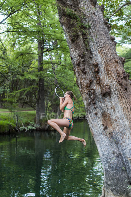 Young woman jumping with rope swing in lake — стоковое фото