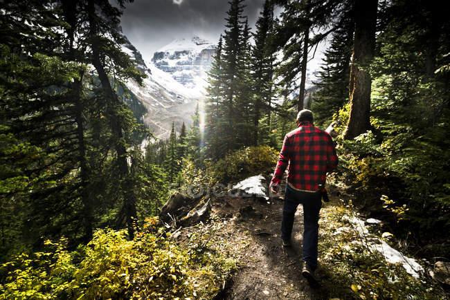 Ein Wanderer zu Fuß durch den Wald in Banff Nationalpark, Kanada mit Schnee bedeckt die Berge im Hintergrund. — Stockfoto