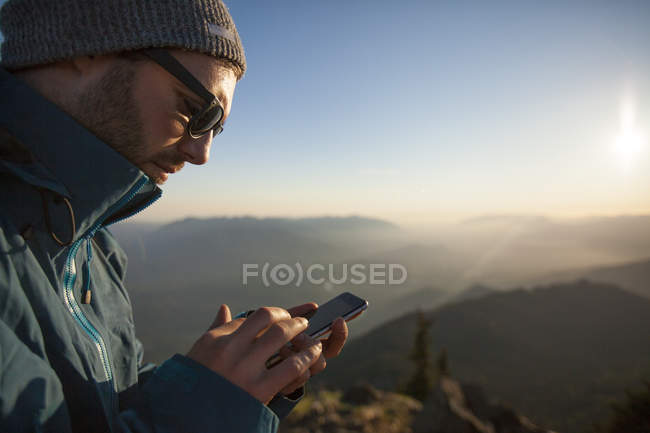 A man uses his smartphone while enjoying the outdoors. — Stock Photo
