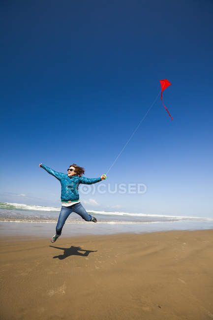 A young woman jumps into the air while flying a red kite in the sky at a beach along the Oregon Coast. — Stock Photo