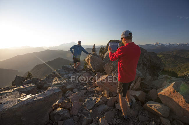 A man uses a tablet to take a picture of his friend on the summit of Sauk Mountain, Washingotn. — Stock Photo