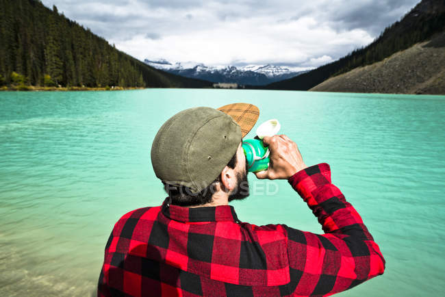Ein mann in einem rot-schwarzen flanell trinkt etwas wasser am rand des louise sees im banff nationalpark. — Stockfoto