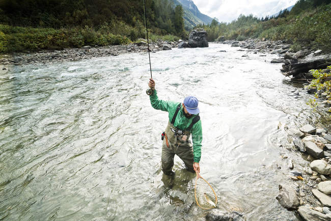 A fisherman reals in his catch in Revelstoke, British Columbia, Canada. — Stock Photo