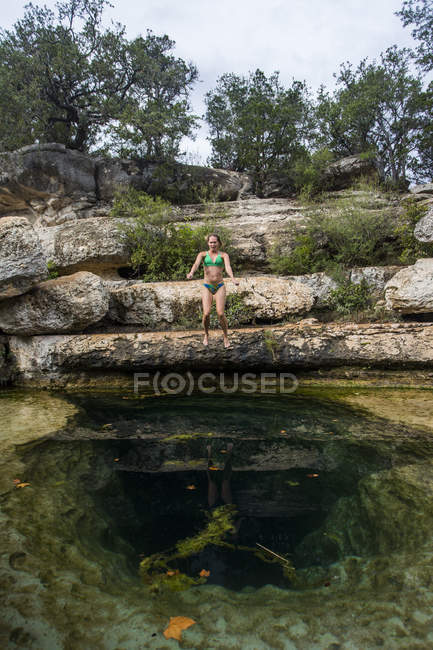 Woman jumping in swimming hole water between rocks — Photo de stock