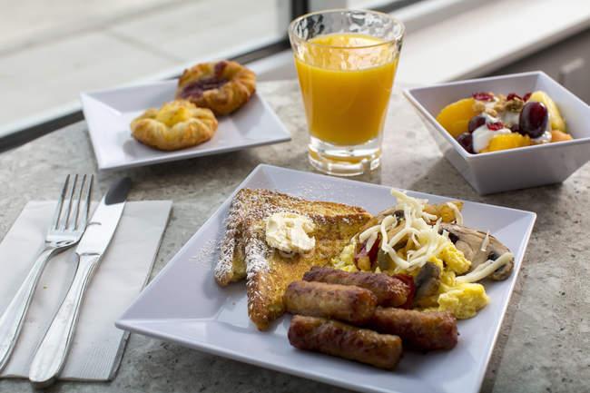 Mesa de desayuno decoradas muy bien con pan tostado, salchichas, queso, crema de fruta al horno empanada y un vaso de batido de mango - foto de stock
