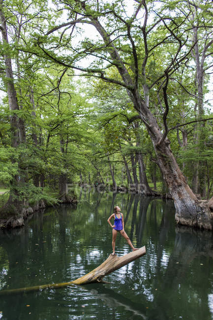 Young woman standing on tree trunk in lake — Photo de stock