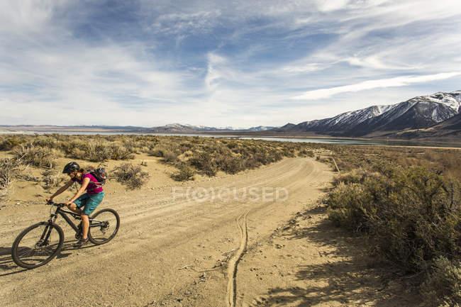 Mulher montar em bicicleta de montanha, na estrada de terra com montanhas ao fundo — Fotografia de Stock
