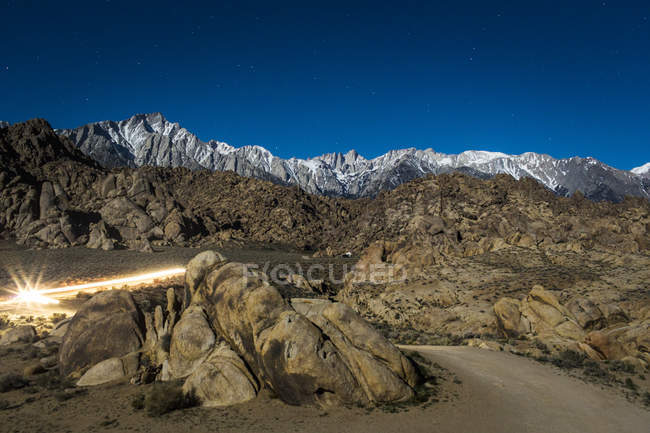 Car lights streak through a nighttime landscape of piles of boulders with a snowy mountain range of jagged peaks in the distance — Stock Photo