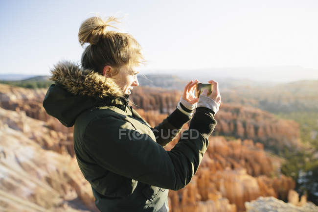 A young woman taking picture of Bryce Canyon National Park. — Stock Photo