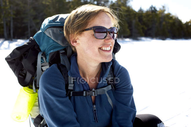 A woman pauses while snowshoeing across a frozen Daicey Pond in Baxter State Park, Maine. — Stock Photo