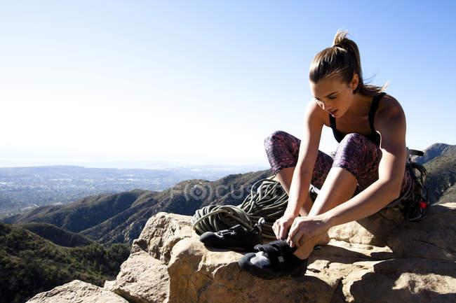 Un Scalatore femminile mette sulle sue scarpe arrampicate seduti in cima alla roccia di Gibilterra inferiore a Santa Barbara, California. Rocca di Gibilterra inferiore fornisce ottimi panorami di Santa Barbara e l'oceano Pacifico — Foto stock