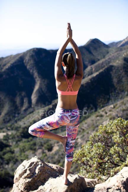 Una donna in pantaloni multicolori esegue albero posa mentre sulla Rocca di Gibilterra inferiore a Santa Barbara, California. Rocca di Gibilterra inferiore fornisce ottimi panorami di Santa Barbara e l'oceano Pacifico — Foto stock