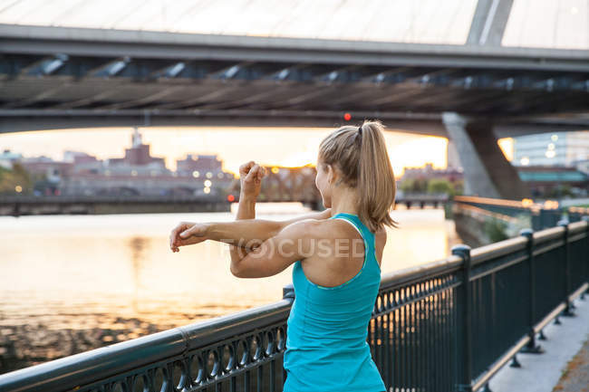 Woman stretching facing a river near a bridge at sunset. — Stock Photo