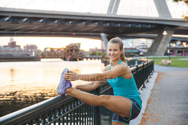 Woman smiling while doing a leg stretch overlooking a river in a park next to a bridge at sunset. — Stock Photo
