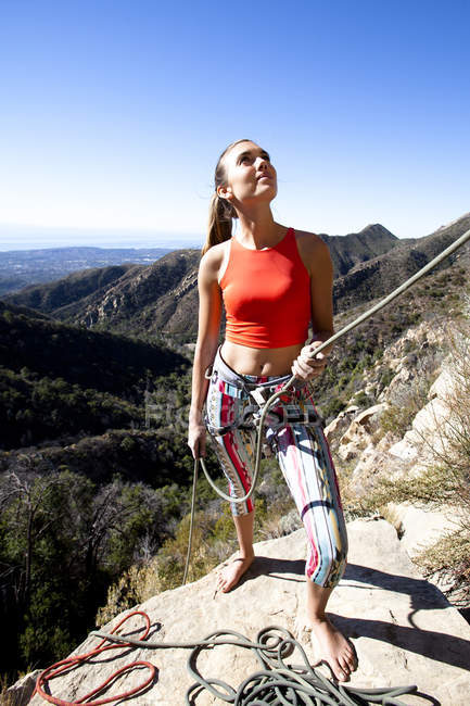A woman wearing a red tank top and striped pants belays while climbing on Lower Gibraltar Rock in Santa Barbara, California.  The Rapture is a very nice and unbelievably well protected route on the left  of Lower Gibraltar Rock. — Stock Photo