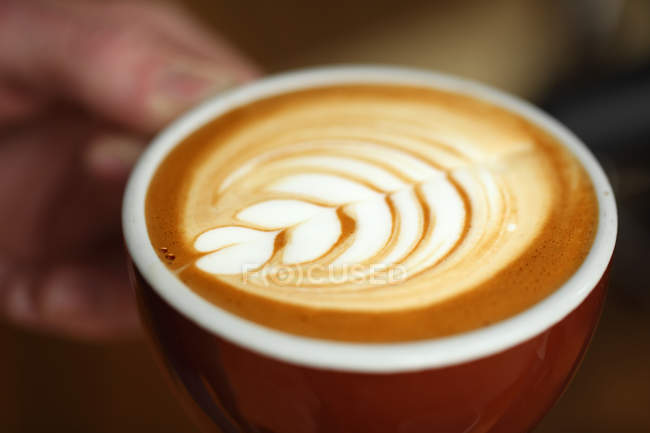 Close-up shot of cup of coffee with latte art in shape of plant — Stock Photo